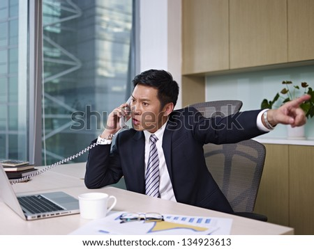 asian businessman talking on phone in office, looking angry. - stock photo