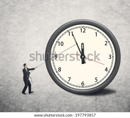 Asian businessman trying to turn back time by pulling on a rope attached to the hands of a clock.  - stock photo