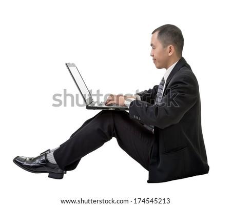 Asian businessman using laptop on ground, full length portrait on white. - stock photo