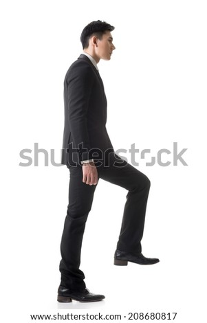 Asian businessman walking up on stairs, full length portrait isolated on white background. - stock photo