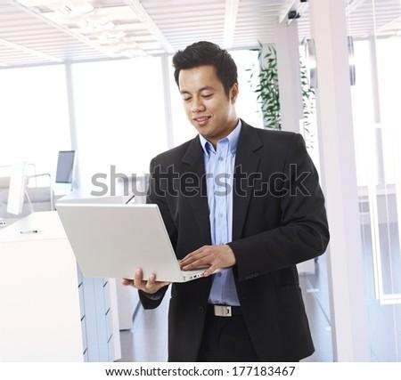 Asian businessman walking, using laptop at office. - stock photo