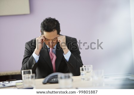 Asian businessman with head in hands - stock photo