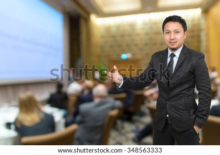 Asian Businessman with welcoming gesture on Abstract blurred photo of conference hall or seminar room with attendee background - stock photo