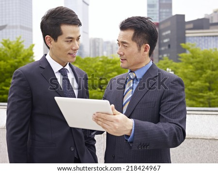 asian businessmen discussing business outdoor. - stock photo