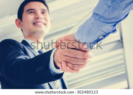 Asian businessmen making handshake with smiling face - greeting, dealing, merger and acquisition concepts - stock photo