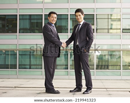 asian businessmen shaking hands looking at camera smiling. - stock photo