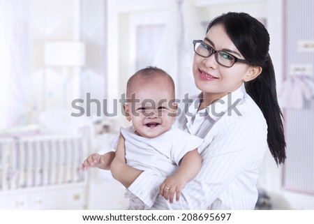 Asian businesswoman and her baby, shot at home - stock photo