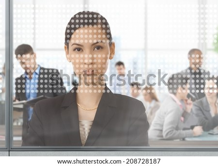 Asian businesswoman at busy office looking through window - stock photo
