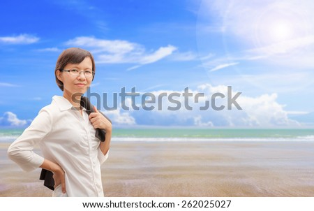 Asian businesswoman at tropical beach - stock photo