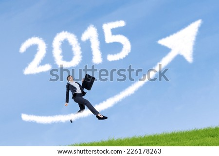 Asian businesswoman carrying briefcase jumping on meadow with upward arrow and number 2015 - stock photo