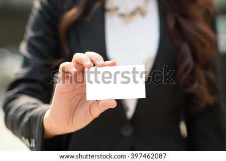 Asian businesswoman holding a blank business card and smiling at the camera - stock photo