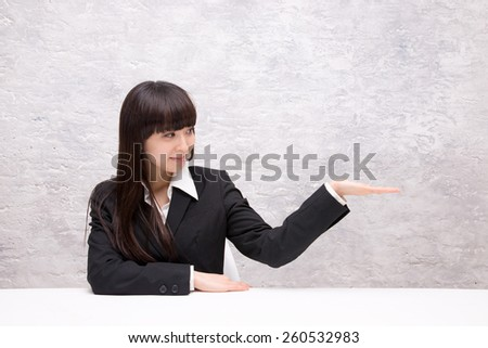 asian businesswoman holding something on her palm - stock photo