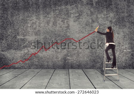 Asian businesswoman is drawing a red line while standing on theladder - stock photo