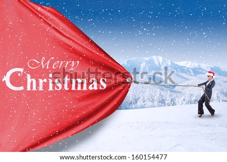 Asian businesswoman is pulling christmas banner on snow mountain - stock photo