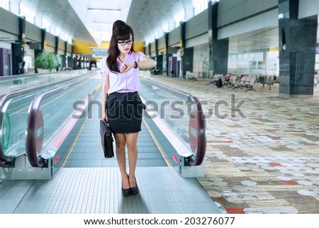 Asian businesswoman looking at her watch. shoot in airport hall - stock photo