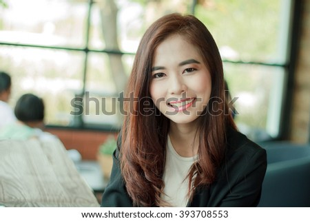 Asian businesswoman smiling while waiting for coffee in the cafe ,soft focus - stock photo