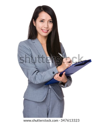 Asian Businesswoman take note on clipboard - stock photo