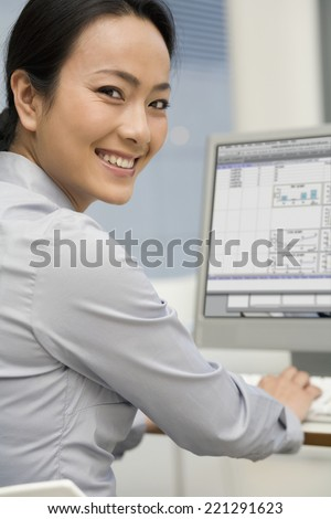 Asian businesswoman typing on computer - stock photo