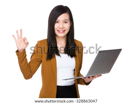 Asian businesswoman use of the laptop computer and ok sign gesture - stock photo