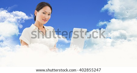 Asian businesswoman using laptop against scenic view of blue sky - stock photo