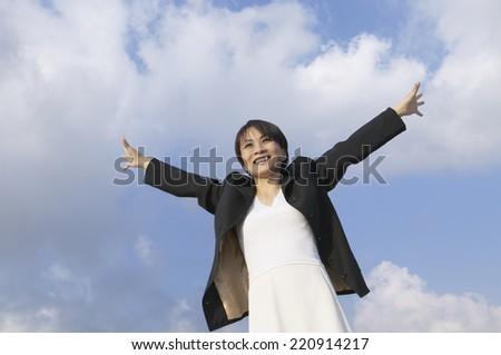 Asian businesswoman with arms outstretched - stock photo
