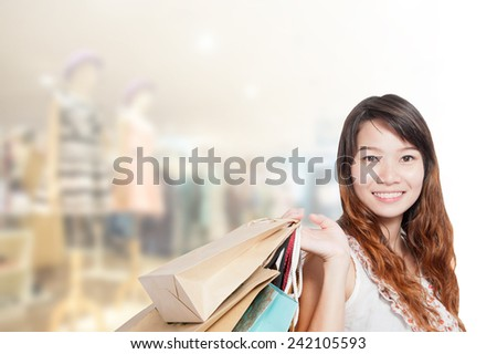 Asian businesswoman with long hair holding a sign board with a red hot sale has shopping mall background. - stock photo