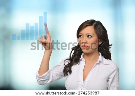 Asian Businesswoman with virtual touch screen inside an office building - stock photo
