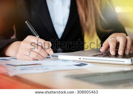 Asian Businesswoman writing a documents and working with laptop. - stock photo