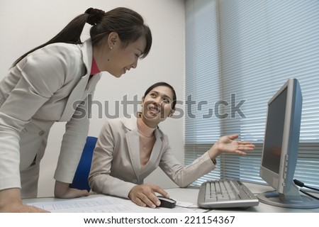 Asian businesswomen looking at computer - stock photo