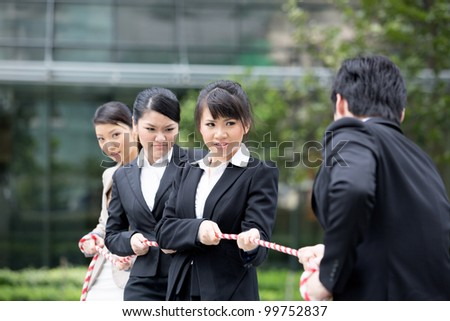 Asian businesswomen playing tug of war against one businessman. - stock photo