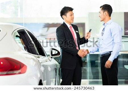 Asian Car Salesman selling auto to customer - stock photo