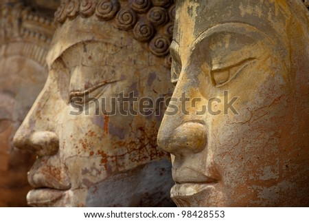 Asian carved stone faces with a serene expression - stock photo