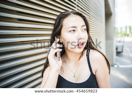 asian casual Woman talking mobile phone against metal line wall in perspective. young girl think and look at far away. Nice hot summer day.  - stock photo