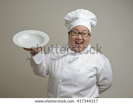 Asian chef holding a plate on plain background - stock photo