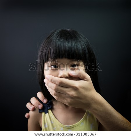 Asian child being kidnapped, with mouth covered by an adult hand - stock photo