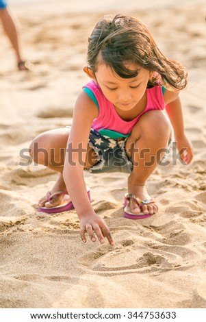 Asian Child Enjoy Writing on The White  Beach Sand, Selective Focus on Hand - stock photo