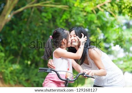 Asian child kissing her mother. Asian family having fun outdoor, biking outdoor. - stock photo
