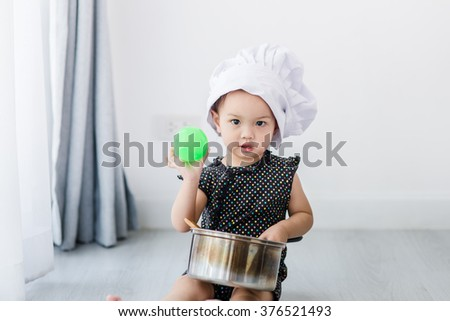 Asian child playing a chef at home. - stock photo