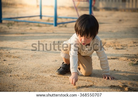 Asian child playing with sand in the playground - stock photo