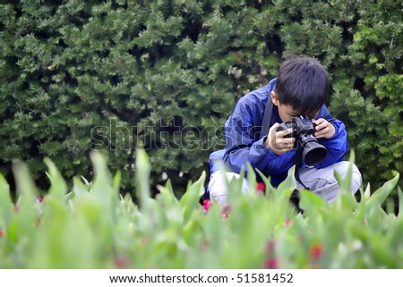 Asian Child taking a flower photo - stock photo