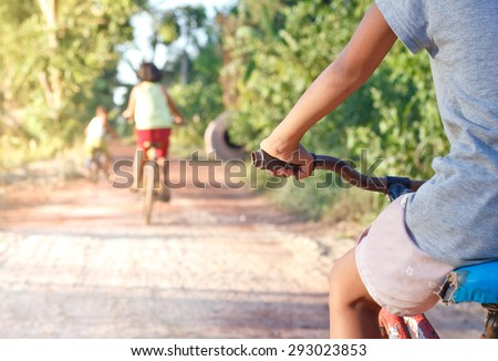 Asian children On Cycle Ride In Countryside.Focused on hand. - stock photo