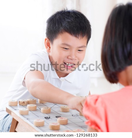 Asian children playing Chinese chess at home. - stock photo