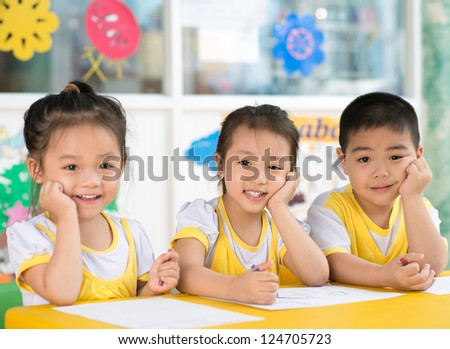 Asian children sitting behind the desk in the room - stock photo