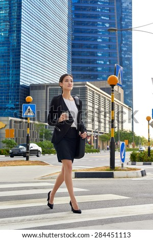 asian chinese business woman crossing street walking to work with coffee drink and bag in urban city district - stock photo