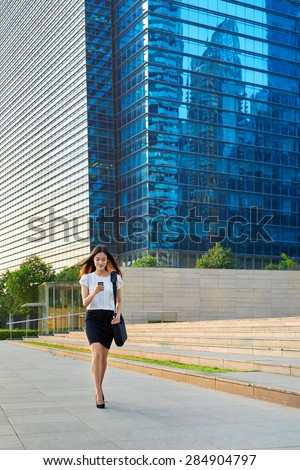 asian chinese businesswoman office worker in downtown business district walking on sidewalk with mobile phone - stock photo