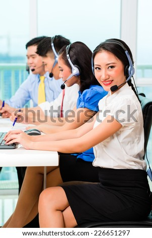 Asian Chinese call center agent team on phone - stock photo