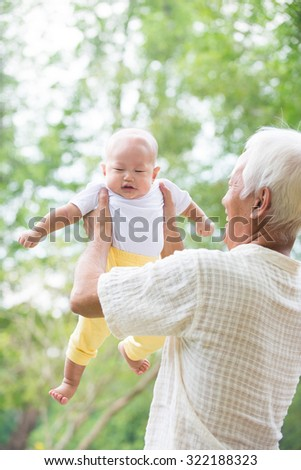 Asian Chinese grandpa and grandson having fun at outdoor garden. - stock photo