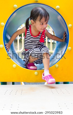 Asian Chinese kid crawling on outdoor playground tube. - stock photo