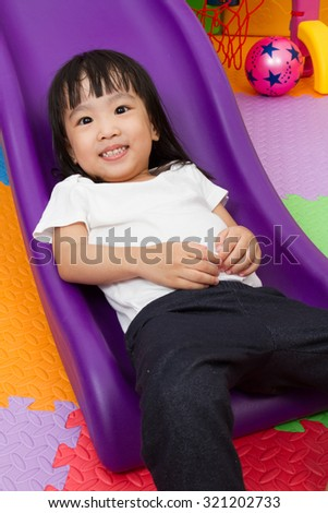 Asian Chinese little girl playing on the slide at indoor colourful playground. - stock photo