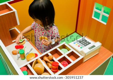 Asian Chinese little girl role-playing at burger store. - stock photo